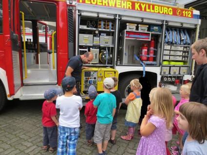 Den Kindern wird das Feuerwehrauto gezeigt