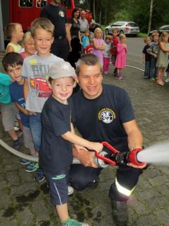 Kinder der Regelgruppen spritzen Wasser aus den Feuerwehrschlauch