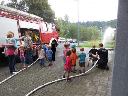 Die Kinder der kleinen altersgemischten Gruppen spritzen Wasser aus den Feuerwehschläuchen